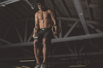 Man Performing Muscle Ups at CrossFit Open